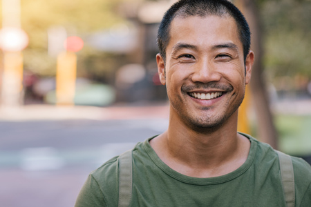 Handsome Asian man standing on a city street and smiling