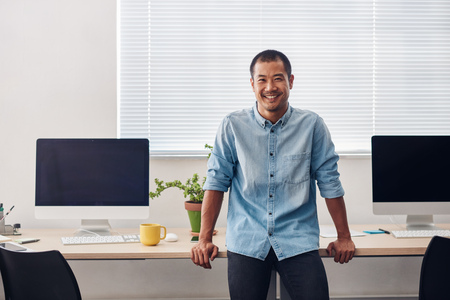 Smiling young Asian designer standing in a modern office