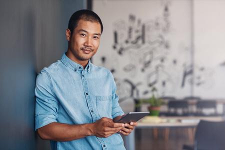 Berzeugter asiatischer Designer, der eine Tablette in einem modernen Büro verwendet Standard-Bild - 77006077