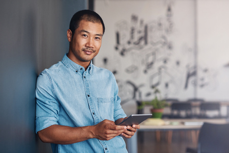 Confident Asian designer using a tablet in a modern office
