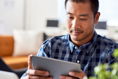 Focused Asian designer using a tablet in a modern office