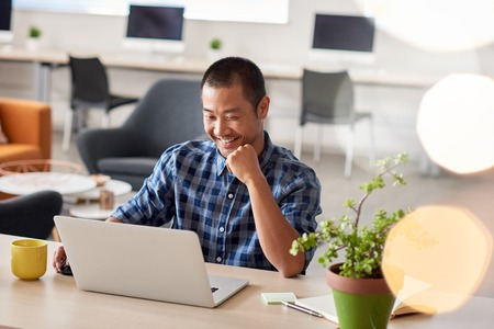 Smiling Asian designer working on a laptop in an office 版權商用圖片