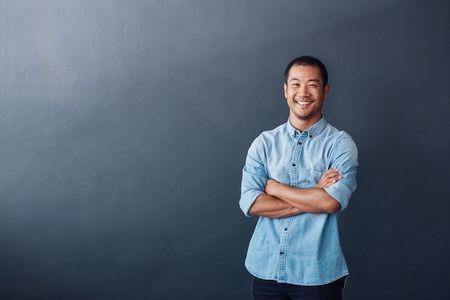 Confident young Asian designer standing in a modern office