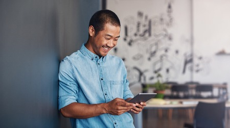 Smiling Asian designer using a tablet in a modern office