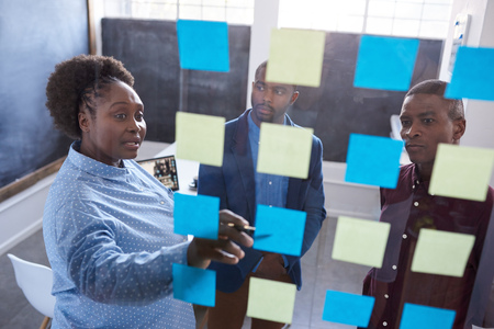strategizing: African coworkers strategizing with sticky notes on a glass wall