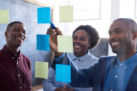 Positive African work colleagues brainstorming together in an office