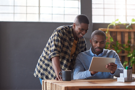 Smiling African coworkers using a digital tablet in an office