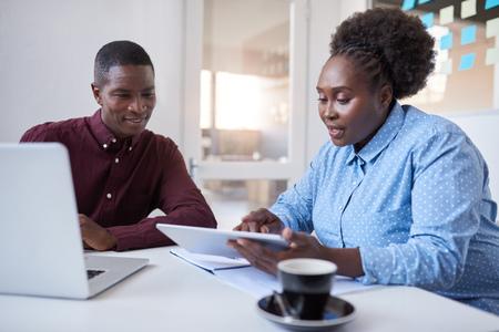 事務所で一緒に技術を使って若いアフリカ ビジネスマン