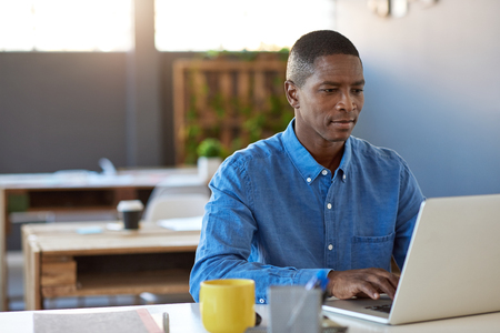 Focused young African businessman sitting confidently at his desk in a large modern office working on a laptop
