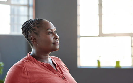 Focused young African businesswoman looking deep in thought while standing alone by windows in a large bright modern office