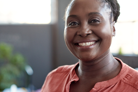 Closeup portrait of a casually dressed young African businesswoman smiling confidently while standing alone in a bright modern office