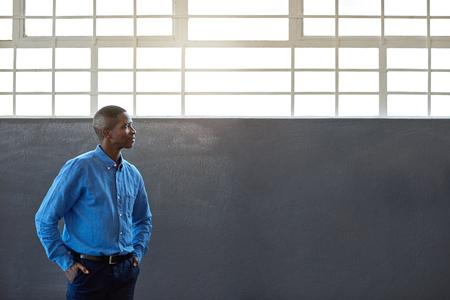 Glimlachende Afrikaanse zakenman die zich met zijn handen op zijn heupen alleen door vensters in een groot modern bureau bevinden die diep in gedachte kijken Stockfoto