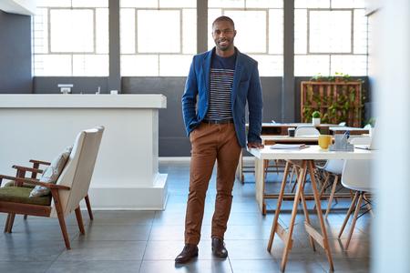 Souriant jeune homme d'affaires africain debout avec confiance dans un bureau moderne Banque d'images - 80738578