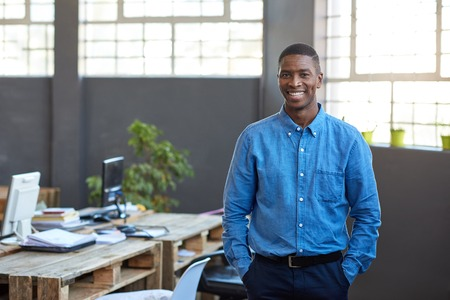 Casually dressed African businessman standing in a modern office Imagens