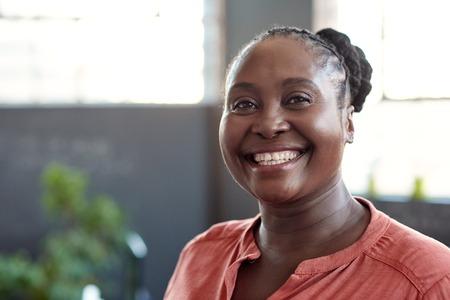 Joven empresaria africana sonriendo con confianza en una oficina