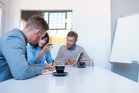 Work colleagues talking business together in an office Imagens