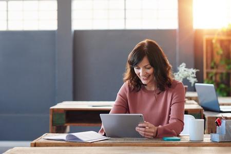젊은 사업가 그녀의 책상에 디지털 태블릿을 사용하여 앉아