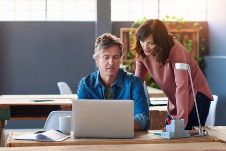 Zwei Kollegen reden über einen Laptop in einem Büro