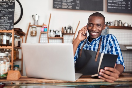 Smiling young African entrepreneur standing at the counter of his cafe talking on a cellphone and reading from a notebook while using a laptop Stock Photo