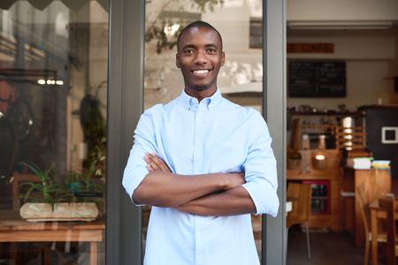 おしゃれなカフェを彼の前に立って腕を交差しながら笑みを浮かべて自信を持って若いアフリカ起業家の肖像画