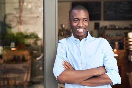 Young African entrepreneur leaning on the door to his cafe photo