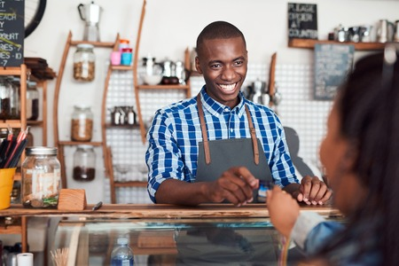 Smiling barista taking a credit card from a cafe customer photo