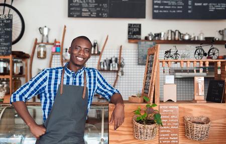 バリスタ カフェでカウンターに寄りかかって笑みを浮かべてください。