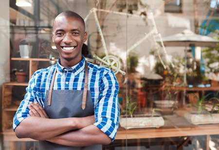 Smiling African entrepreneur standing behind a counter of his cafe