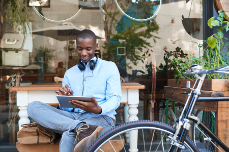 Young man browsing the internet at a sidewalk cafe photo