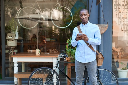 Smiling young man standing in the street reading text messages photo