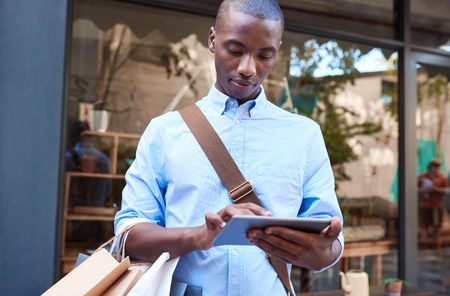 Young man using a tablet while shopping in the city photo