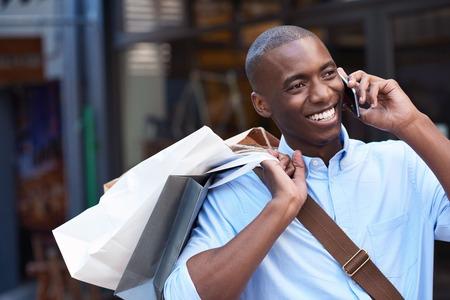 若い男の外の彼の携帯電話で話しているキャリーのショッピング バッグ 写真素材