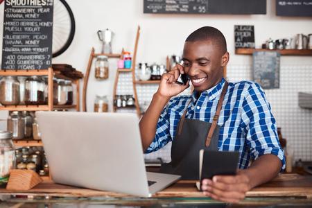 Smiling entrepreneur hard at work on his cafe business