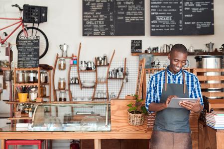デジタル タブレットを使用して彼のカフェで立っている若い起業家