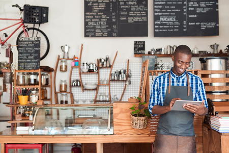 Young entrepreneur standing in his cafe using a digital tablet