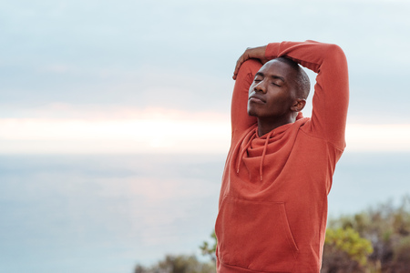 Young African man stretching before a run along the ocean