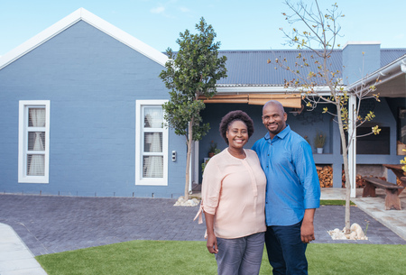 Smiling African couple standing outside on their lawn
