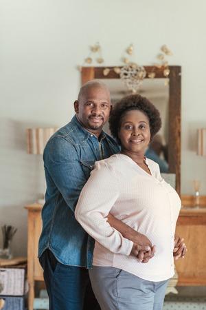 Glimlachend Afrikaans paar dat zich liefdevol samen in hun woonkamer bevindt Stockfoto