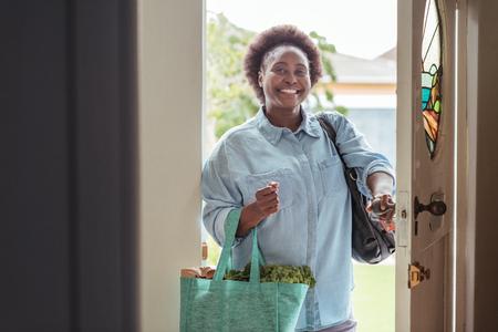 Sonriente mujer africana llegar a casa de compras Foto de archivo