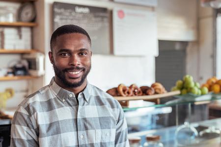 彼のカフェに立っている若いアフリカの起業家を笑顔 写真素材
