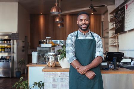 彼のカフェのカウンターに立って微笑むアフリカの起業家