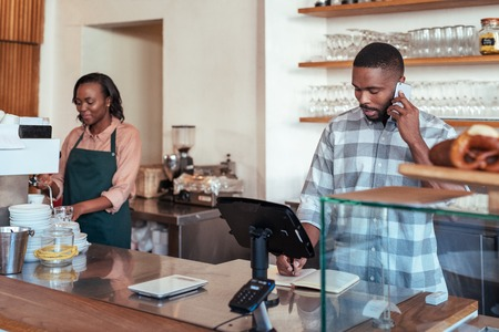 Young African entrepreneurs working together behind their cafe counter