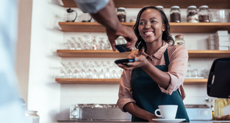 Smiling barista using nfc technology for payment from a customer
