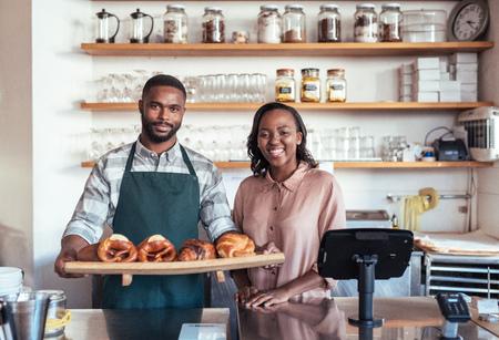 アフリカの起業家がベーカリーカウンターの後ろに焼いたグッズを持って微笑む 写真素材