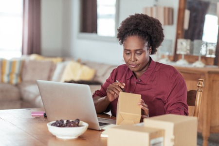 Young African woman labeling packages while working from home