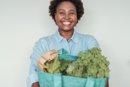 Smiling young African woman holding a bag of groceries Imagens