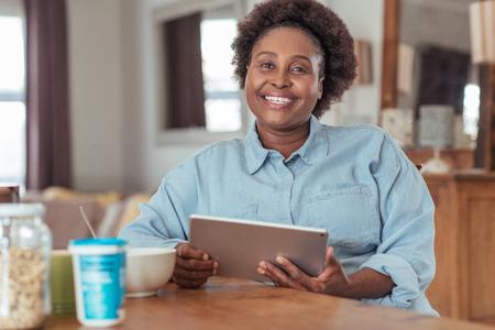 タブレットを家で使用しながら朝食を食べて笑顔の女性 写真素材