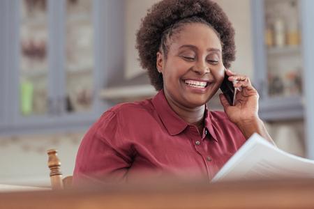 アフリカ女性閲覧書類を微笑し、彼女の携帯電話で話しています。 写真素材