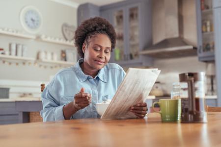 가정에서 아침 식사하는 동안 신문을 읽는 젊은 여자