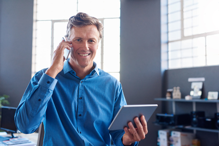 Smiling businessman talking on his cellphone and using a tablet
